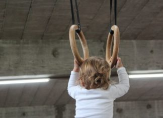child holding onto indoor monkey bars
