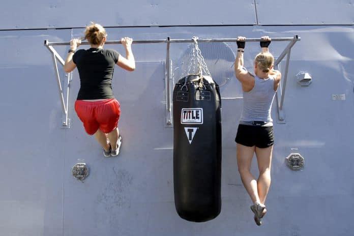 athletic ladies swinging on stall bars