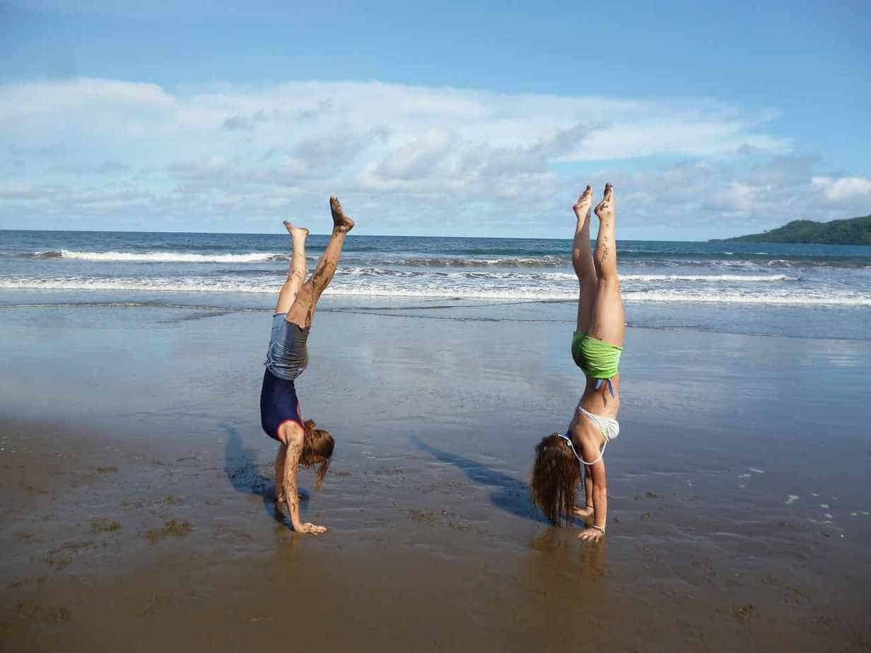girls doing handstands on the beach