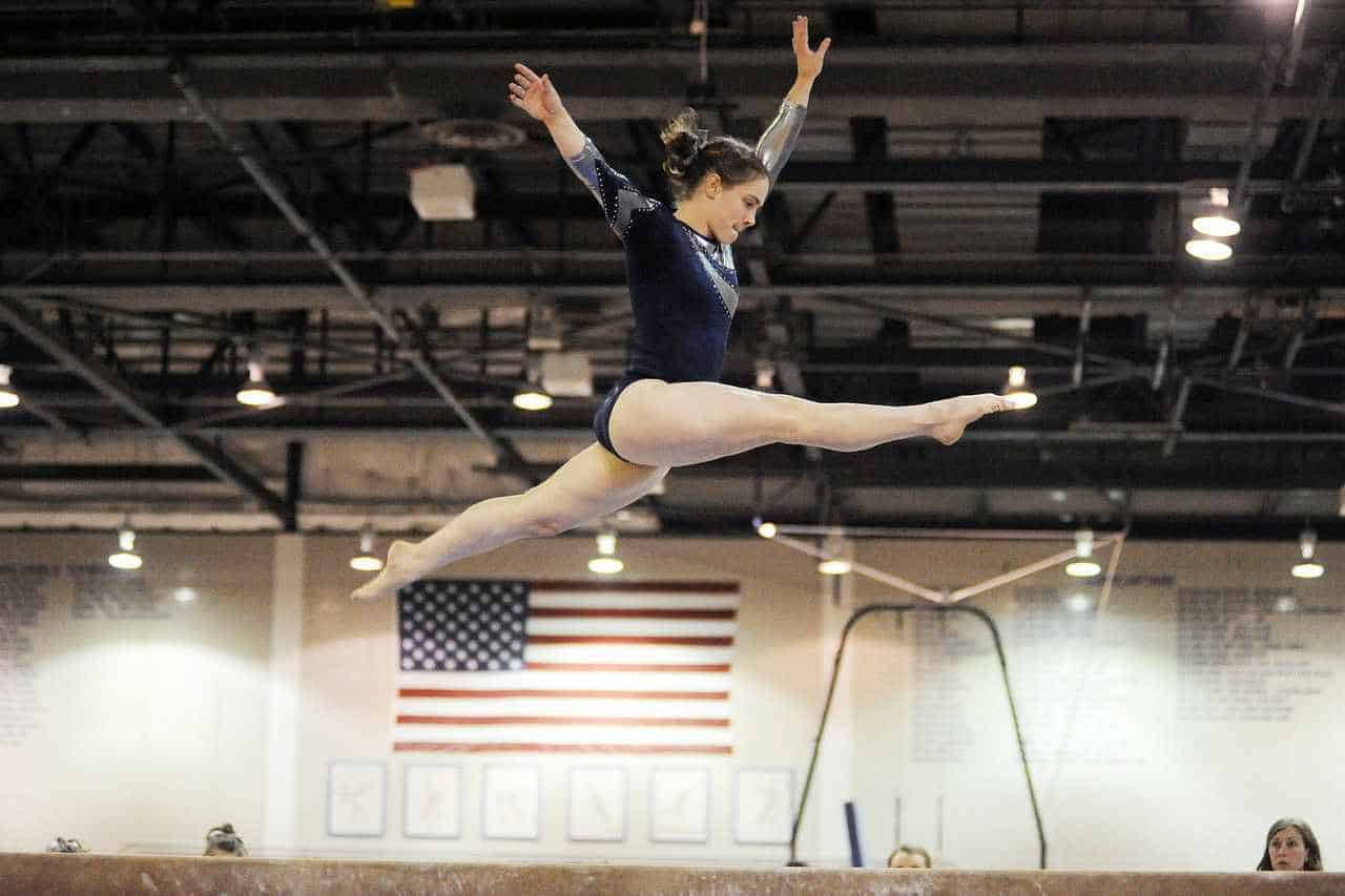 gymnast in air above beam