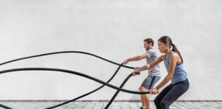 man and women using battle ropes