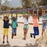 kids swinging on monkey bar