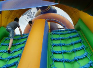 children playing on inflatable obstacle course