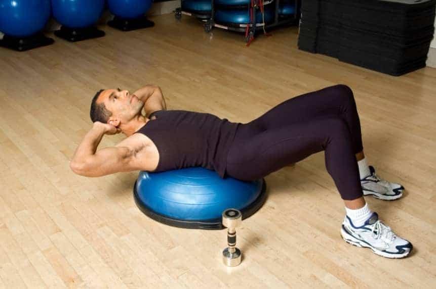 man exercising on bosu ball