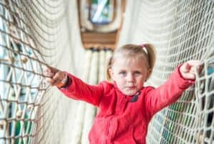 toddler climbing through rope tunnel bridge